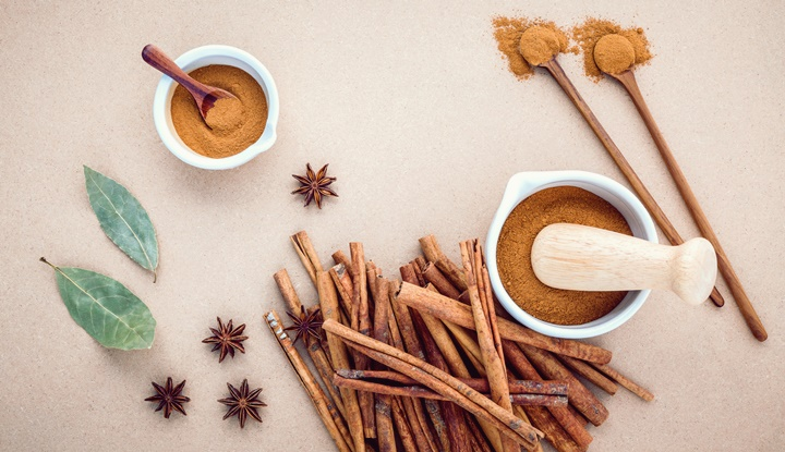 Composition of cinnamon stick and cinnamon powder in white morta