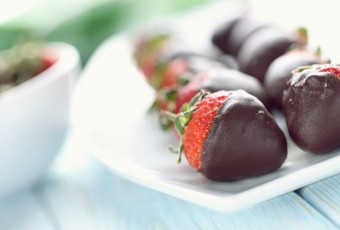 Fresh strawberries dipped in dark chocolate on blue wooden backg