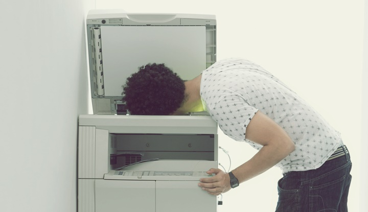 Man putting his head in copy machine in hallway