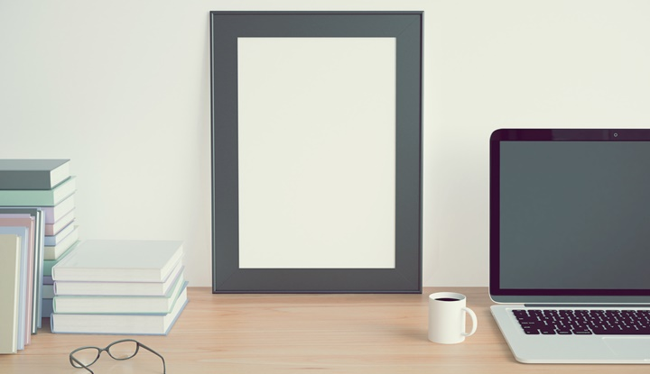 Blank picture frame on wooden table with books
