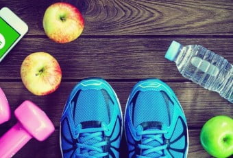 Fitness, healthy and active lifestyles Concept, Bottle of water, dumbbells, sport shoes, smartphone and apples on wood background. copy space for text.  Top view
