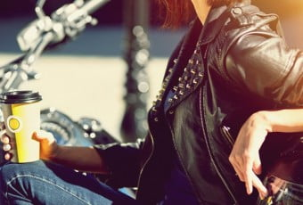 Biker girl on a motorcycle drinking coffee