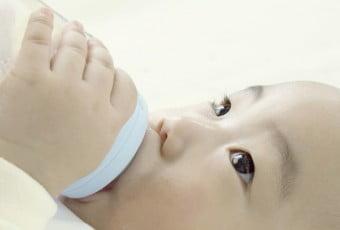 a baby sucking a nursing bottle