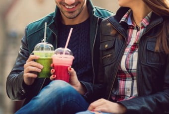 Happy couple drinking smoothies