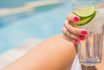 Woman holding refreshing cold drink by the pool