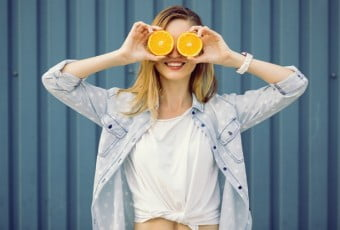 Smiling woman holding two orange in hands