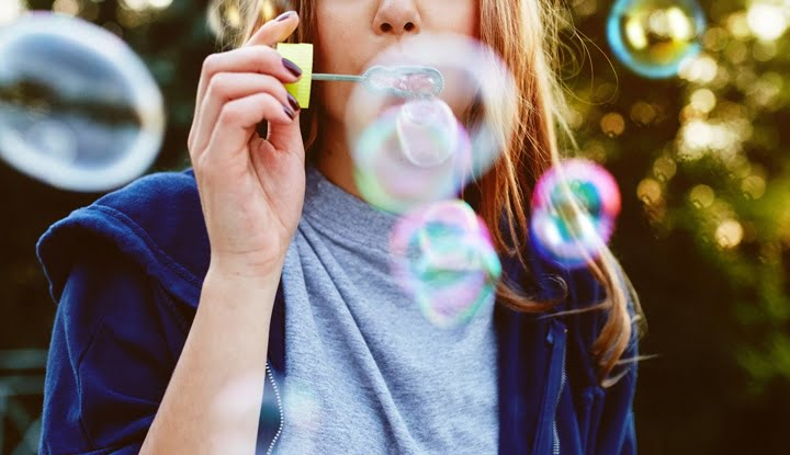 Young woman portrait blowing soap bubbles