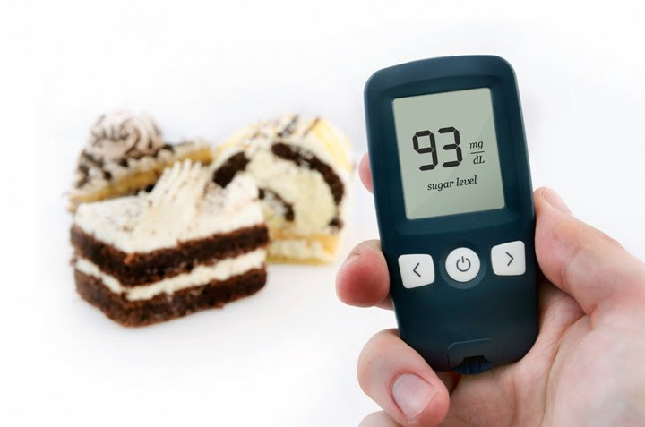 Hand holding meter. Diabetes doing glucose level test. Cake in background